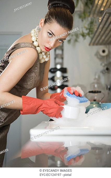 Young woman holding cups by sink in kitchen