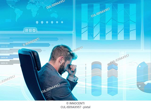 Man sitting in chair, stressed expression, data on graphical screen behind him