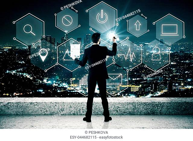 Back view of businessman drawing abstract digital business icons on rooftop. Illuminated night city background. Future concept. Double exposure