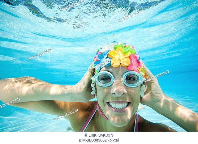 Hispanic woman in retro swimming cap underwater in swimming pool