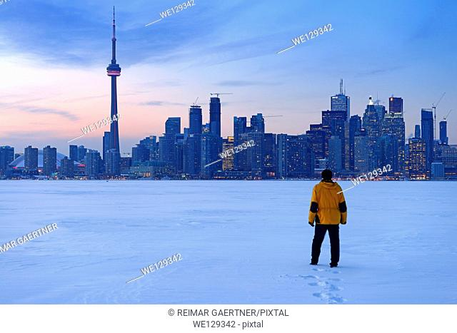 Man walking in fresh snow on frozen Lake Ontario with Toronto city skyline in winter
