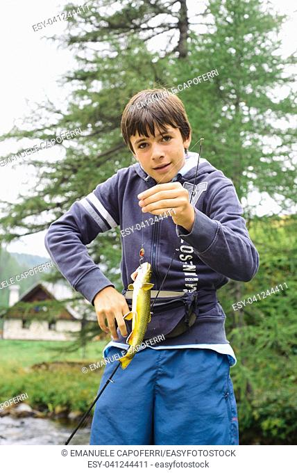 little boy with trout caught in mountain river in the alps