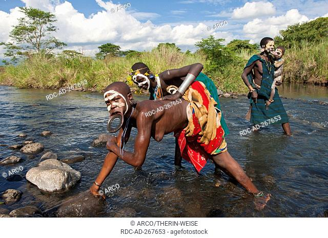 Surma women with lip plate, in river, Kibish, Omo River Valley, Ethiopia