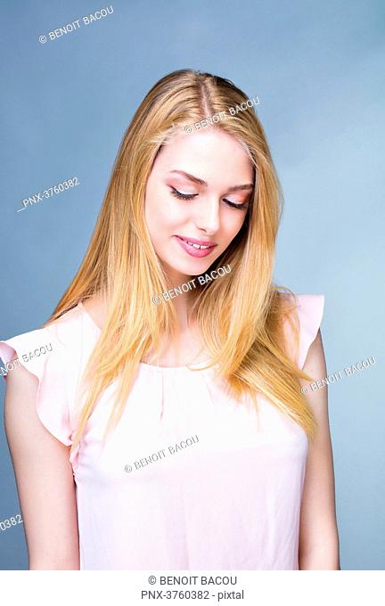 Portrait of a smiling young woman, head bent down