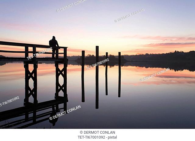 Silhouette of man on pier at sunrise