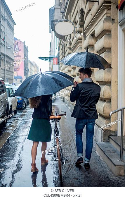 Couple with umbrella on morning commute, Budapest, Hungary