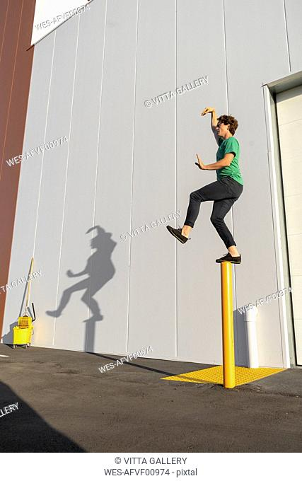 Acrobat standing on pole, casting shadow at cleaning bucket