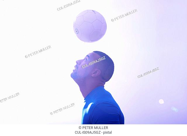Studio shot of young male soccer player keeping ball mid air with header