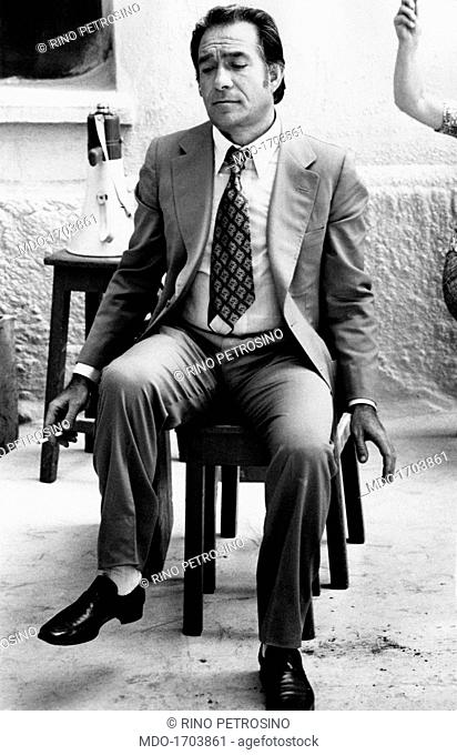 Ugo Tognazzi sits on a chair smoking a cigarette. The actor Ugo Tognazzi relaxes smoking a cigarette in a pause during the filming of the movie Lady Caliph; the...