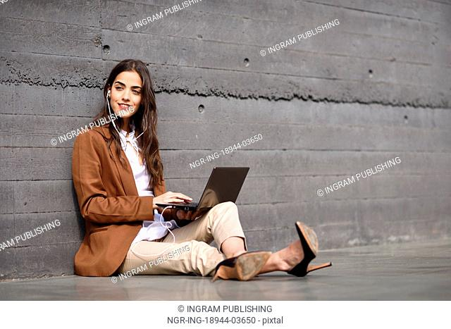 Young businesswoman sitting on floor looking at her laptop computer. Beautiful woman wearing formal wear using earphones