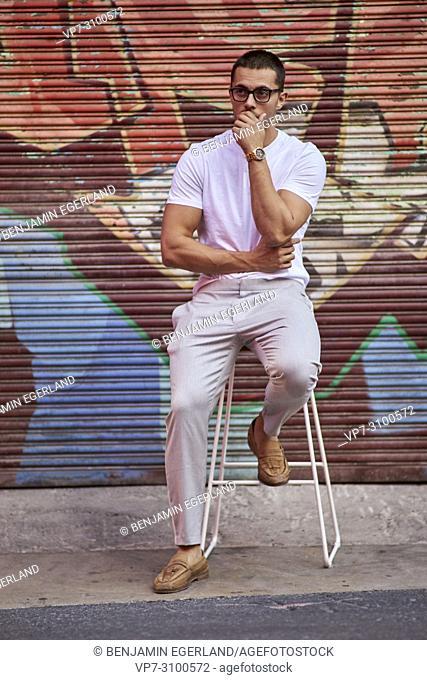 Australia, Adelaide, mens fashion blogger Reno Marrasso posing on a stool at street, thoughtful