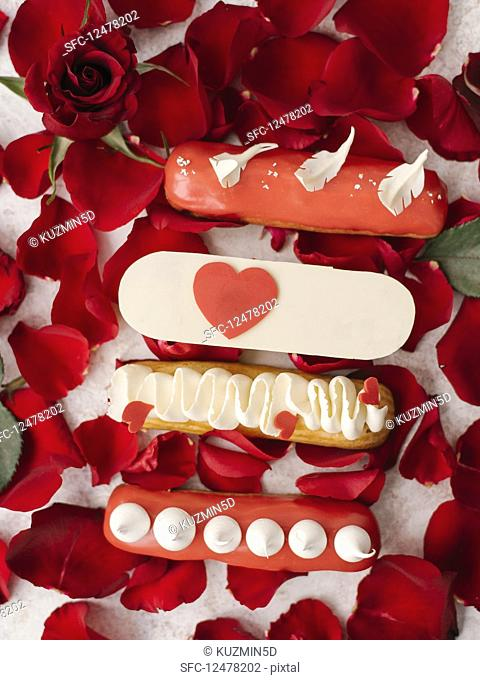 Eclairs with decorations and red rose petals
