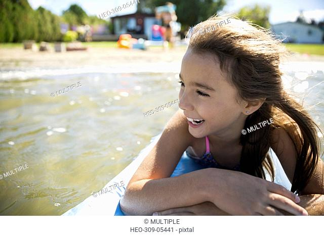 Smiling girl laying on inflatable raft on sunny summer lake