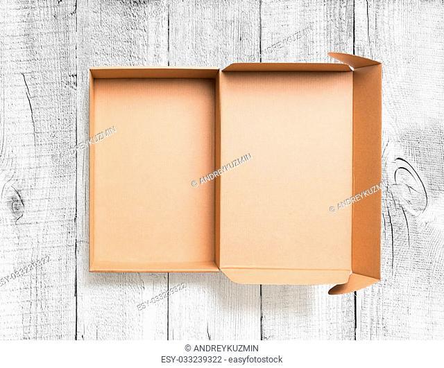 Open cardboard box top view on wooden floor