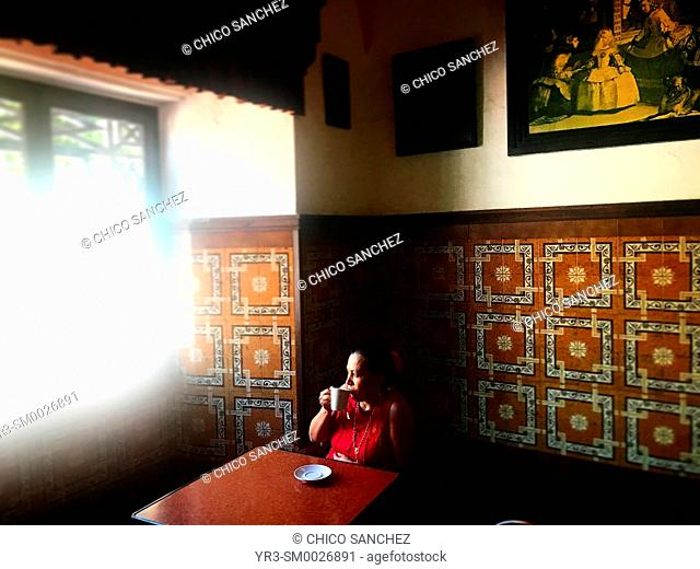 A woman drinks coffee in a traditional Spanish coffee shop in the Sierra of Grazalema, Andalucia, Spain