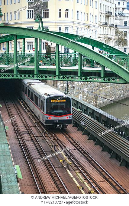 Metro U-Bahn train comes out of a tunnel and goes under Zollamtssteg Bridge while crossing the river in Vienna, Austria