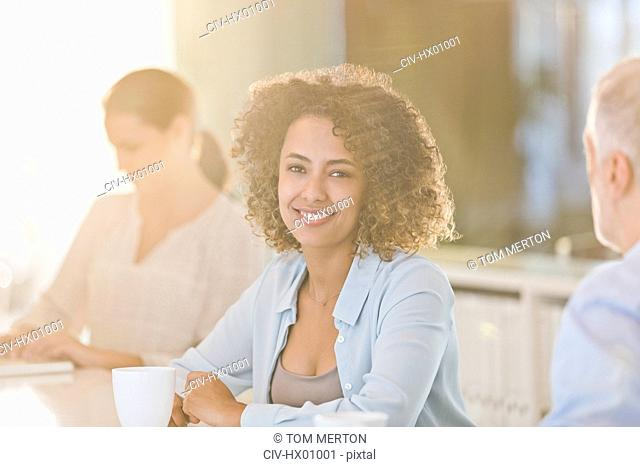 Portrait smiling businesswoman drinking coffee in meeting