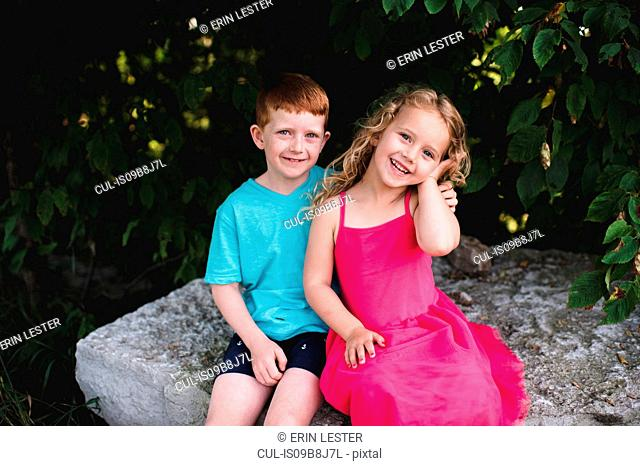 Portrait of boy and sister sitting on rock