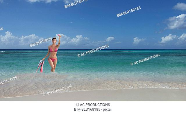 Caucasian woman wading on beach with flippers and snorkel