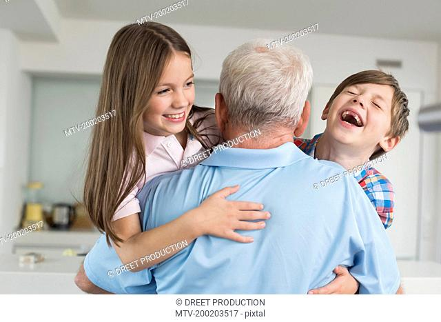 Grandfather hugging happy grandchildren