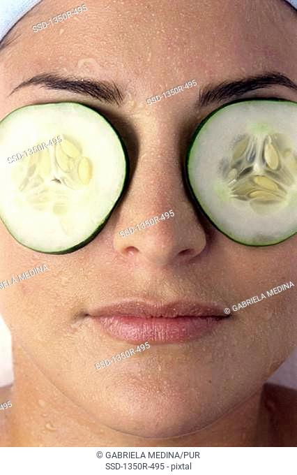 Close-up of a young woman with cucumber slices on her eyes
