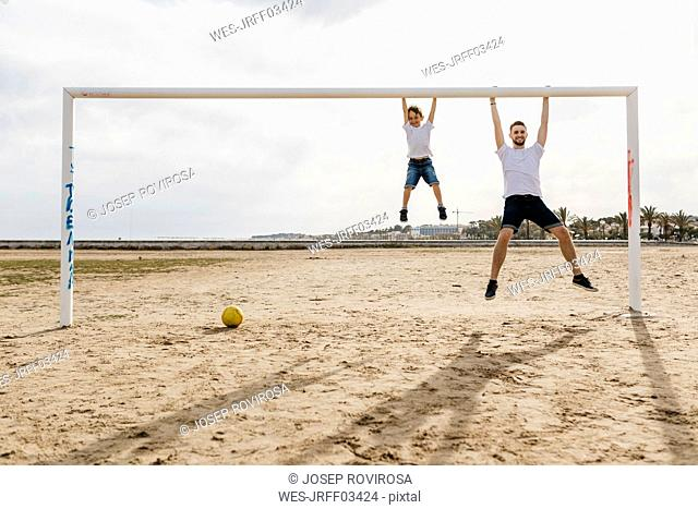 Man and boy hanging from the goal while playing soccer on the beach