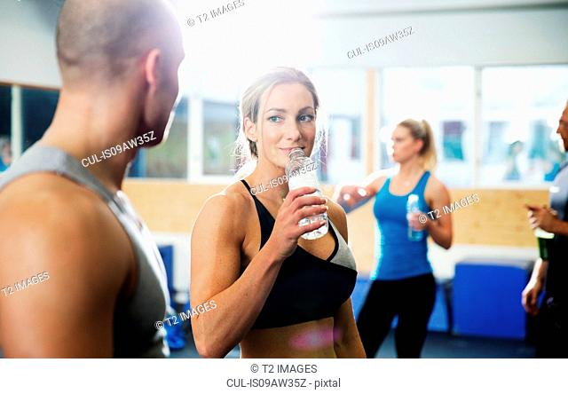 Men and women drinking bottled water in gym