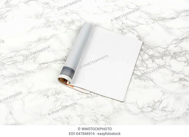 Mock-up magazine or catalog on white marble table. Blank page or notepad on stone background. Blank page or notepad for mockups or simulations
