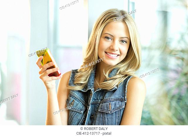 Woman using cell phone at window