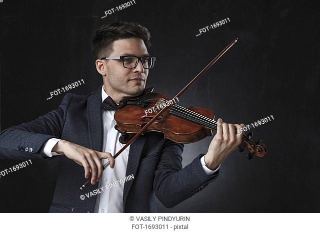 Smiling handsome violinist playing violin against black background