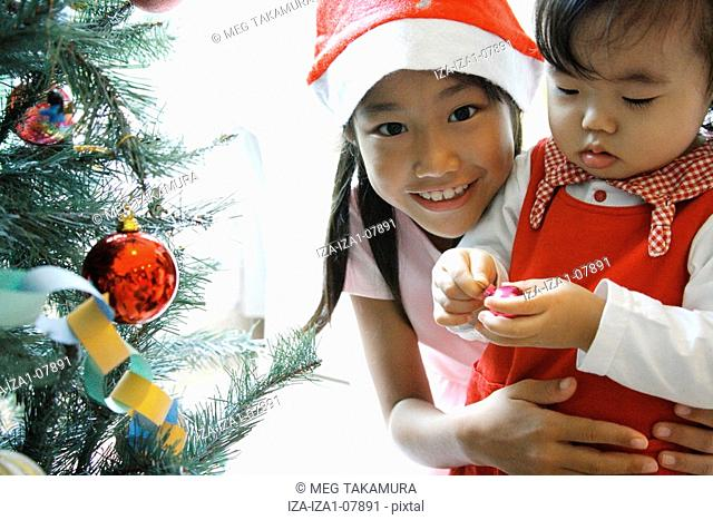 Close-up of a baby girl holding a Christmas ornament with her sister smiling behind her
