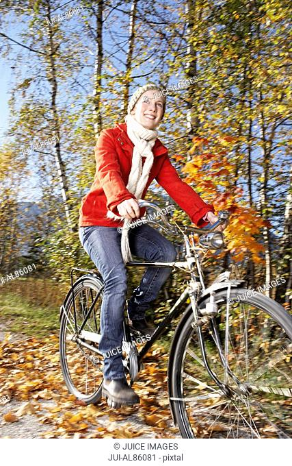 Woman riding bicycle on path in autumn