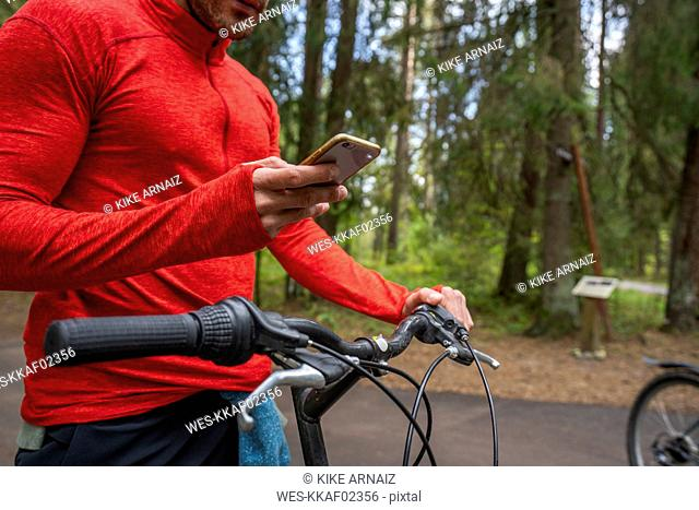 Mountain biker using smartphone in a forest