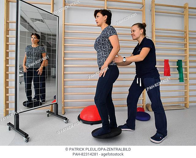 A therapist (R) exercises with a patient in the rehab section of brandmed, a cross-border health center in the Polish city Slubice