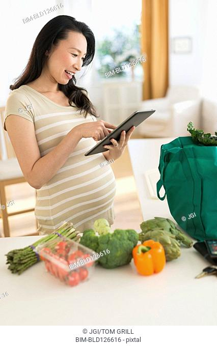 Pregnant Japanese woman using digital tablet in kitchen