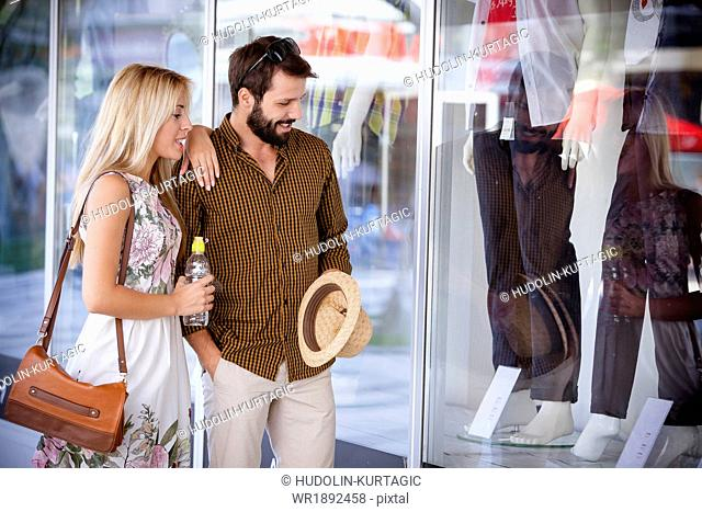 Young couple looking at fashion shop window