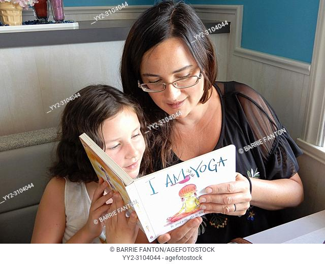 Mother and Daughter Reading Book Together, Perry, New York, USA