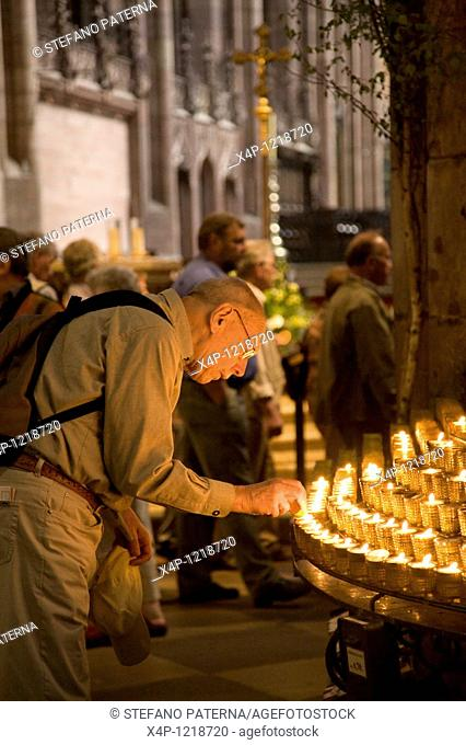 A mature visitor in Freiburg Muenster is lighting a candle. Freiburg's townscape is dominated by its magnificent Muenster on the bustling market square