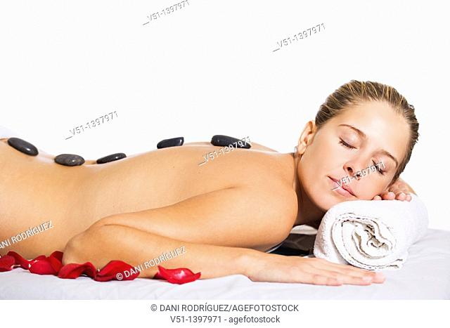 Blonde woman in massage with stones und petals