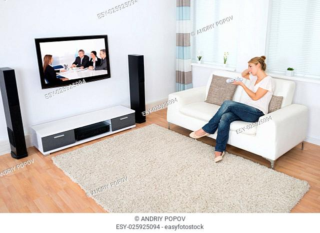 Full length of young woman watching TV while sitting on sofa in living room