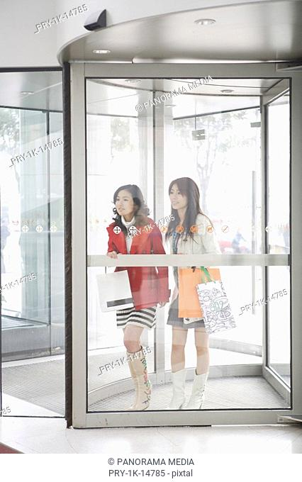 Young women at the doorway of shopping mall