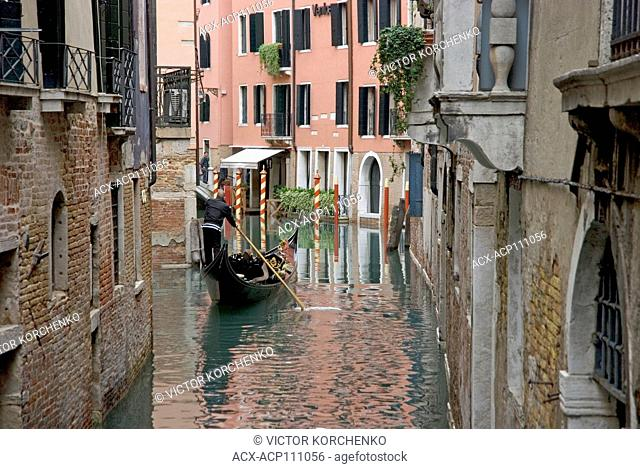 Gondola carrying tourists on a canal in Venice