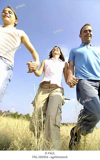 Low angle view of family walking in field