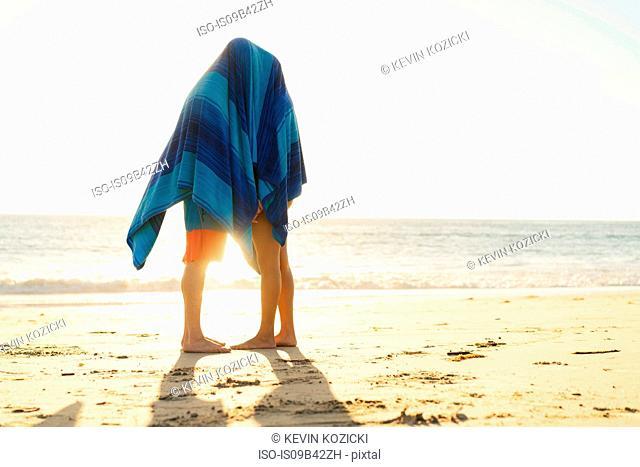 Couple hiding under blanket on Newport Beach, California, USA
