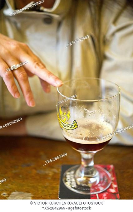 Woman pointing at empty beer glass at A la Mort Subite tavern in Brussels