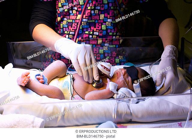 Nurse listening to baby girl's heartbeat in hospital