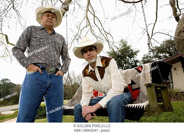 Portrait of Tex-Mex father and son in in front yard of house