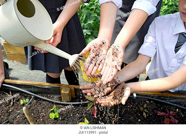 Middle school students with dirty potting soil hands gardening washing hands with watering can