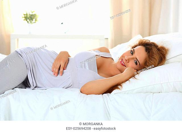 Beautiful smiling woman laying in her bed in the morning. Morning time. New wonderful day beginning. Copy space