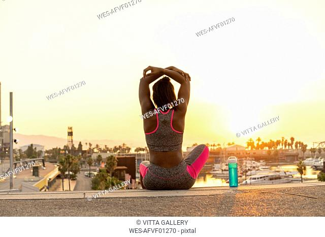 Spain, Barcelona, young man stretching arm at sunrise